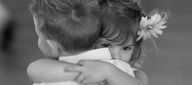 a black and white photo of a young girl and boy hugging. The girl has an innocent daisy in her hair.