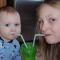 Two young children sharing a drink with separate straws and smiles!