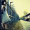 An beautiufl asian girl in a sundress waiting with her back to a gate facing a country road.