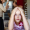 A little girl with her hands up to her forehead in stress, a mother and father fighting in the backround. The mother looks like she has bills in her hand and the dad is holding a young little boy.