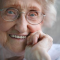 An elderly woman with glasses smiling and healthy.