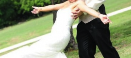 A happy couple in the grass. A wife in her wedding dress as her husband is catching her during a playful fall.