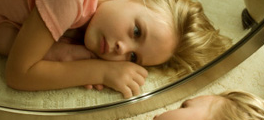A young blonde girl lying on the floor, looking at herself with a sad expression in the mirror. She is lying on the floor.