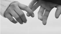 A couple barely touching hands, but reaching out to each other.